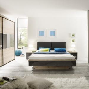 Asteria to kolekcja mebli do sypialni, która wprowadza do wnętrza ciepły klimat. Zestawienie kolorystyczne, łączące jasny dąb san remo z szarymi elementami w wysokim połysku, zapewnia  przyjazny dla oka efekt, sprzyjający odpoczynkowi. Fot. Helvetia Wieruszów.