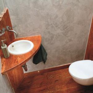Toaleta dla gości z czerwonym trawertynem. Projekt: Daria Zaremba. Fot. Bartosz Jarosz.