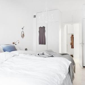 W przestronnej sypialni udało się wygospodarować miejsce na pojemną garderobę, ukrytą w wysokiej zabudowie okalającej z dwóch stron wejście do pomieszczenia. Fot. Vastanhem.se.