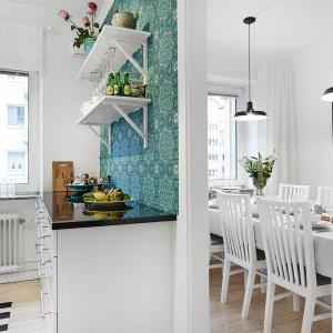 Ścianę oddzielającą kuchnię od jadalni ozdobiono wzorzystą tapetą w turkusowym kolorze, delikatnie korespondującym z barwą płytek nad blatem. Fot. Vastanhem.se.