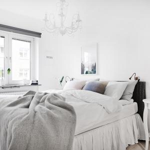 Sypialnia urządzona została w jasnych kolorach. Mimo tego jednak ciężko odmówić jej przytulności. Za sprawą dużej ilości tkanin oraz stylizowanych mebli zyskała ona bardzo ciepły charakter. Fot. Vastanhem.se.