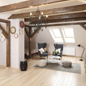Strefę wypoczynkową stanowią dwa eleganckie fotele, lekki stolik kawowy i przytulne pufy, ustawione na puchatym, szarym dywanie. Projekt: Piotr Stanisz. Fot. Bartosz Jarosz.
