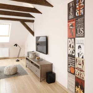 Na ścianie zawisł telewizor nad elegancką, postarzaną komodą, pełniącą funkcję szafki RTV. Projekt: Piotr Stanisz. Fot. Bartosz Jarosz.