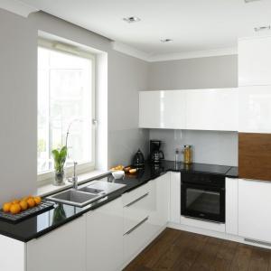 Wąską kuchnię urządzono w bieli, szarości i ciepłym kolorze drewna. Ścianę pomalowano na szaro, a nad blatem przekryto dodatkowo szkłem. Projekt: Karolina Łuczyńska. Fot. Bartosz Jarosz.