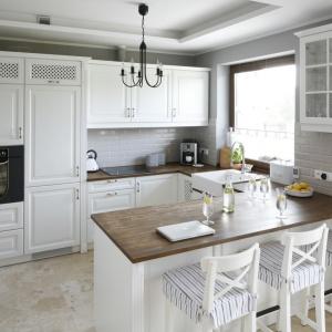Aranżacja tej kuchni jest utrzymana w angielskim stylu. Meble w kolorze złamanej bieli są zdobne, z dekoracyjnymi frezowaniami i uchwytami, a wieńczy je drewniany blat. Ścianę wykończono pięknymi szarymi kaflami. Projekt: Beata Ignasiak. Fot. Bartosz Jarosz.