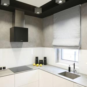 W kuchni urządzonej w minimalistycznym, oszczędnym stylu ścianę nad blatem utrzymano w dwóch kolorach: bieli i szarości. Ta ostatnia ma postać betonowego tynku. Projekt: Karolina Stanek-Szadujko. Fot. Bartosz Jarosz.