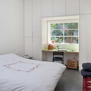 Oprócz zabudowy ściany, na której są drzwi, zabudować można także ścianę z oknem - tworząc okienną ramę z zamykanych szafek. Fot. Galit Deutsch.