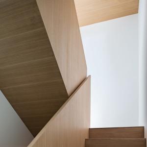 Centrum domu, komunikującym ze sobą wszystkie strefy jest w przeważającej części drewniana klatka schodowa. Drewno jest tutaj nie tylko na stopniach, ale również pokrywa całe balustrady. Projekt: TACT Design. Fot. David Giral.