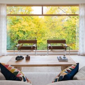 Ogromne panoramiczne okno nie tylko oświetla pokój dzienny, ale także wprowadza do niego dodatkowy kolor w postaci zieleni. W otoczeniu natury można się zrelaksować siadając na dwóch wygodnych fotelach. Projekt: TACT Design. Fot. David Giral.