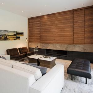 Domownicy mogą się zrelaksować w specjalnie do tego stworzonym pokoju z kominkiem. Do wypoczynku zapraszają wygodne meble, a przytulność buduje drewniana zabudowa nad kominkiem, odseparowana od źródła ognia naturalnym kamieniem. Projekt: TACT Design. Fot. David Giral.