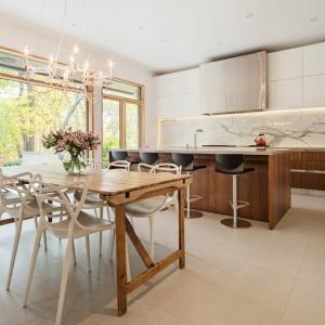 Z przodu domu urządzono strefę jadalnianą, pięknie oświetloną naturalnym światłem, wpadającym do środka przez ogromne okno. Jadalnię połączono z elegancką kuchnią, a funkcje te oddziela umownie duża wyspa. Projekt: TACT Design. Fot. David Giral.