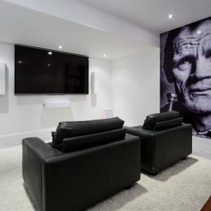 W domu urządzono oddzielną salę audio-telewizyjną. Zaprojektowano ją w kolorystyce starych filmów - czerni i bieli, a najmocniejszym elementem dekoracyjnym jest fototapeta ze zdjęciem muzyka jazzowego Cheta Bakera. Projekt: TACT Design. Fot. David Giral.