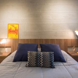 Barwna kolorystyka kontynuowana jest w sypialni. Tutaj przede wszystkim za sprawą żółtej lampki nocnej i dekoracyjnej grafiki. Projekt: Semerene Arquitetura Interior. Fot. Joana França.
