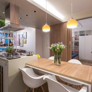 Nad wyspą kuchenną zawisły dwie żółte lampy, wprowadzające kolor do przestrzeni kuchni. Projekt: Semerene Arquitetura Interior. Fot. Joana França.