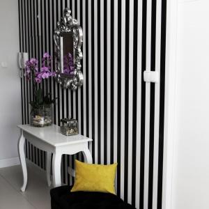 Ścianę w przedpokoju udekorowano odważną dwukolorową tapetą w pionowe pasy. Przestrzeń ożywia żółta poduszka dekoracyjna, która znalazła swoje miejsce na niewielkim, czarnym podnóżku. Projekt: Chalupko Design. Fot. Chalupko Design.