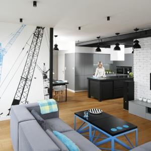 Mieszkanie w Warszawie zaprojektowano w stylu industrialnym z dużą dozą turkusu, wprowadzonego do wnętrz za sprawą grafiki na ścianie, stolika kawowego oraz dekoracyjnych poduszek. Projekt: Monika i Adam Bronikowscy. Fot. Bartosz Jarosz.
