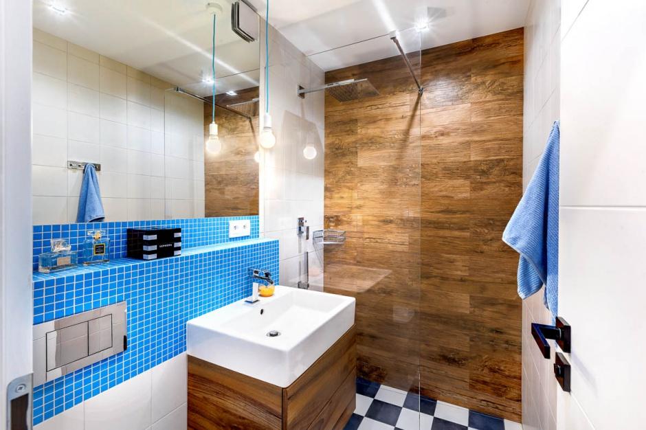 W łazience kontynuowana jest kolorystyka z kuchni. Fragment ściany pod dużym lustrem wykończono błękitną mozaiką, z którą harmonizują edisonowskie żarówki wiszące na błękitnych oplotach. Projekt:  COCO Pracownia projektowania wnętrz. Fot. Łukasz Markowicz.