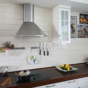 Aranżacja kuchni utrzymana została w stylu retro, a ścianę nad blatem ozdobiono płytkami imitującymi tradycyjne kafle. Projekt: Magdalena Misaczek. Fot. Bartosz Jarosz.