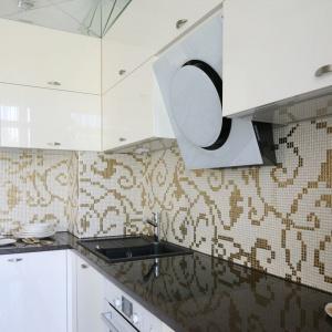 Ścianę nad blatem zdobi ciekawa mozaika - drobne płytki układają się w złoty wzór, imitujący winorośl. Projekt: Agnieszka Hajdas-Obajtek. Fot. Bartosz Jarosz.