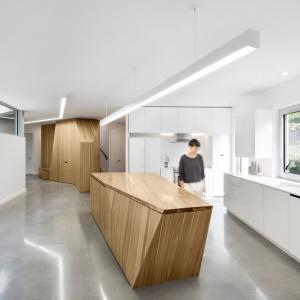 Wnętrze zorganizowano w oparciu o masywne, drewniane bryły. Jedną z nich jest oryginalna wyspa kuchenna o geometrycznej formie, wskazująca ciąg komunikacyjny pomiędzy salonem, a holem. Projekt: Paul Bernier architecte. Fot. Adrien Williams.