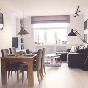 Nad stołem jadalnianym zawisła metalowa, industrialna lampa, harmonizująca z metalowym zegarem na ścianie w stylu retro. Projekt: Meblościanka Studio. Fot. Maua Fotografia.