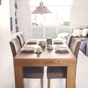 Jadalnia to solidny, drewniany stół oraz tapicerowane krzesła, które szarością swojej tapicerki harmonizują z wystrojem salonu i spajają wizualnie obie strefy. Projekt: Meblościanka Studio. Fot. Maua Fotografia.