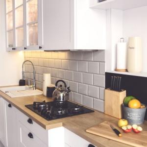 W kuchni postawiono na białe meble w klasycznej stylistyce, zwieńczone drewnianym blatem i czarnymi uchwytami. Uroku całości dodają kafle nad blatem. Projekt: Meblościanka Studio. Fot. Maua Fotografia.