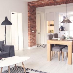 Salon, jadalnię i kuchnię urządzono w jednej linii, łącząc pokój dzienny z przestrzenią spożywania posiłków. Kuchnia zajmuje oddzielne pomieszczenie, częściowo otwarte na jadalnię, częściowo przesłonięte wysoką, funkcjonalną zabudową. Projekt: Meblościanka Studio. Fot. Maua Fotografia.