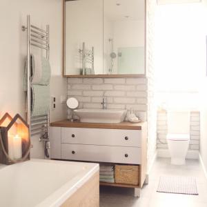 W łazience panuje neutralna kolorystyka i prostota aranżacyjna. Obecność białej cegły jest nawiązaniem do tego samego materiału w innych pomieszczeniach mieszkania i podkreśla jedność przestrzeni całego wnętrza. Projekt: Meblościanka Studio. Fot. Maua Fotografia.