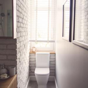 Wąską wnękę w łazience wykorzystano na montaż wc. Projekt: Meblościanka Studio. Fot. Maua Fotografia.