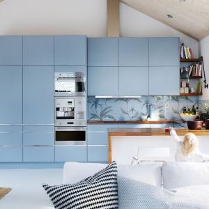 Aranżacja kuchni, w której niebieski całkowicie zdominował przestrzeń. Matowe fronty mebli kuchennych utrzymane są w kolorze baby blue, a ścianę nad blatem zdobi tapeta w niebiesko-srebrnym kolorze. Fot. Ballingslov.