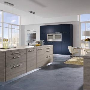 Wysoka zabudowa w dość ciemnym niebieskim kolorze przełamuje spokojne fronty w wybarwieniu drewna. Całość prezentuje się elegancko i stylowo. Fot. Alno.
