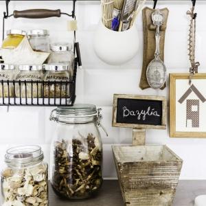 Wiklinowe kosze, drewniane elementy i stylizowany reling podkreślają prowansalski charakter kuchni. Projekt: Decoroom. Fot. Ayuko Studio.