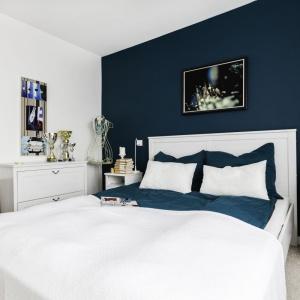 Sypialnia właścicielki została urządzona w eleganckim, lekko marynistycznym stylu. Stało się tak za sprawą połączenia bieli i pięknego, morskiego koloru na ścianie za wezgłowiem łóżka. Projekt: Decoroom. Fot. Ayuko Studio.