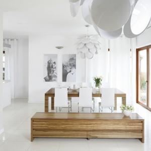 """Niezwykle elegancki dom został w całości urządzony w bieli i ciepłym odcieniu drewna z pięknym, poziomym rysunkiem słojów. Nie inaczej jest w jadalni. Tutaj drewno przełamano białymi krzesłami, a przytulność podkreśla lampa o """"puszystej"""" formie. Projekt: Agnieszka Ludwinowska. Fot. Bartosz Jarosz."""