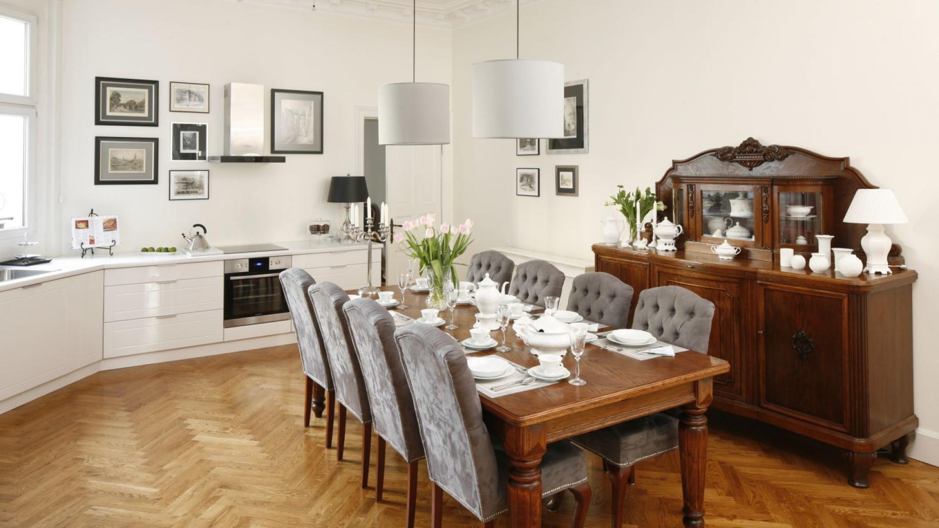 Mieszkanie w starej kamienicy zostało urządzone w mieszance stylów: nowoczesnym i klasycznym. Jadalnię urządzono w kuchni - ta jest biała i stanowi jasne tło dla bardziej solidnych, drewnianych mebli i tapicerowanych krzeseł w szarym kolorze. Projekt: Iwona Kurkowska. Fot. Bartosz Jarosz.