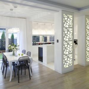 Jadalnię zlokalizowano w sąsiedztwie dużego okna, które wpuszcza do środka dużo dziennego światła oraz obok kuchni, oddzielonej od ciągu komunikacyjnego podświetlanymi ażurowymi panelami. Projekt: Katarzyna Mikulska-Sękalska. Fot. Bartosz Jarosz.