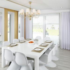 Duża jadalnia aż dla dziesięciu osób stanowi niezależne pomieszczenie urządzone w jasnych kolorach: podłogę wyściełają bielone płytki jak drewno, stół i pantonowskie krzesła są białe, a światło do wnętrza wpuszcza duże, ogromne okna. Projekt: Dominik Respondek. Fot. Bartosz Jarosz.