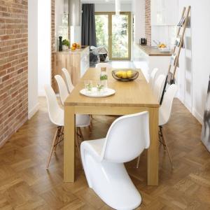 Jadalnię i kuchnię urządzono w jednym rzędzie, prowadzącym dalej w głąb domu, do salonu. Podłogę zdobi tradycyjny parkiet, harmonizujący z drewnianym stołem. Dominację naturalnych materiałów, jak drewno i cegła przełamują białe krzesła. Projekt: Agata Piltz. Fot. Bartosz Jarosz.