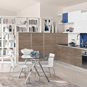 Granicę pomiędzy kuchnią i salonem wyznacza zabudowa kuchenna, której przedłużeniem jest elegancka, biała biblioteczka z licznymi otwartym półkami, przepuszczającymi światło. Fot. Cucine Lube, model Naturalmente Brava.