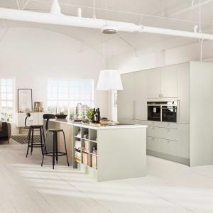 Idealny przykład na to jak wielofunkcyjnym meblem może być wyspa. W tej nowoczesnej kuchni w stylu skandynawskim pełni rolę domowego baru, strefy zmywania, gotowania oraz kompaktowej biblioteczki. Fot. Sigdal, kuchnia Line.
