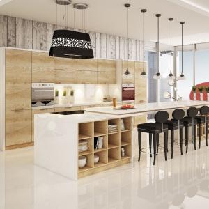 Bardzo długa wyspa kuchenna zbudowana jest z dwóch brył połączonych ze sobą długim blatem, pełniącym funkcję stołu. W jednym i drugim kubiku zaplanowano otwarte półki, pełniące funkcję między innymi biblioteczki. Książki przechowywać można również na asymetrycznych półkach poprowadzonych od podłogi do sufitu na granicy salonu i kuchni. Fot. Moelke Kuchnie, model Moelkepunto Dąb Santiago.