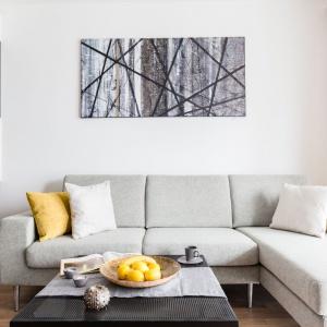 Nad łóżkiem zawisła abstrakcyjna grafika o mocno geometrycznym motywie, która przewrotnie nawiązuje swoim wyglądem zarówno do ściany nad blatem, jak i do lampy nad stolikiem. Projekt: Decoroom.