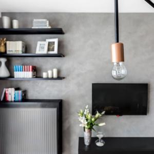 Surowa, przetarta faktura betonowej ściany wspaniale współgra z odsłoniętymi żarówkami i zabudową grzejnika, wykonaną z perforowanej, czarnej blachy. Projekt: Decoroom.