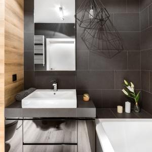 W łazience zestawiono ciemną szarość z ciepłym kolorem drewna. Projekt: Decoroom.