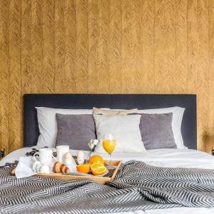 Po obu stronach łóżka zawisły lampy o szklanych, okrągłych koszach w brązowym kolorze. Pełnią funkcję lampek nocnych. Projekt: Decoroom.