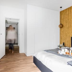 W sypialni wzrok przyciąga złota tapeta z tłoczonym wzorem, zdobiąca ścianę za wezgłowiem łóżka. Projekt: Decoroom.