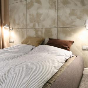 Ciekawie ozdobiona ściana za łóżkiem będzie zwracać na siebie uwagę. W tym wnętrzu zdecydowano się na miękkie panele, które dodatkowo nadają sypialni przytulności. Projekt: Lucyna Kołodziejska. Fot. Bartosz Jarosz.