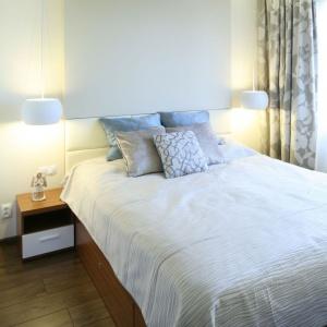Jasna sypialnia urządzona z myślą o parze. Lampki zamontowane po obu stronach łóżka zapewniają komfort podczas czytania. Projekt: Agnieszka Hajdas-Obajtek. Fot. Bartosz Jarosz.