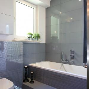 Szarość, biel i elementy błękitu doskonale pasują do tej niewielkiej łazienki. Błyszczące płytki o dużym formacie optycznie powiększają wnętrze. Projekt: Arkadiusz Grzędzicki. Fot. Bartosz Jarosz.